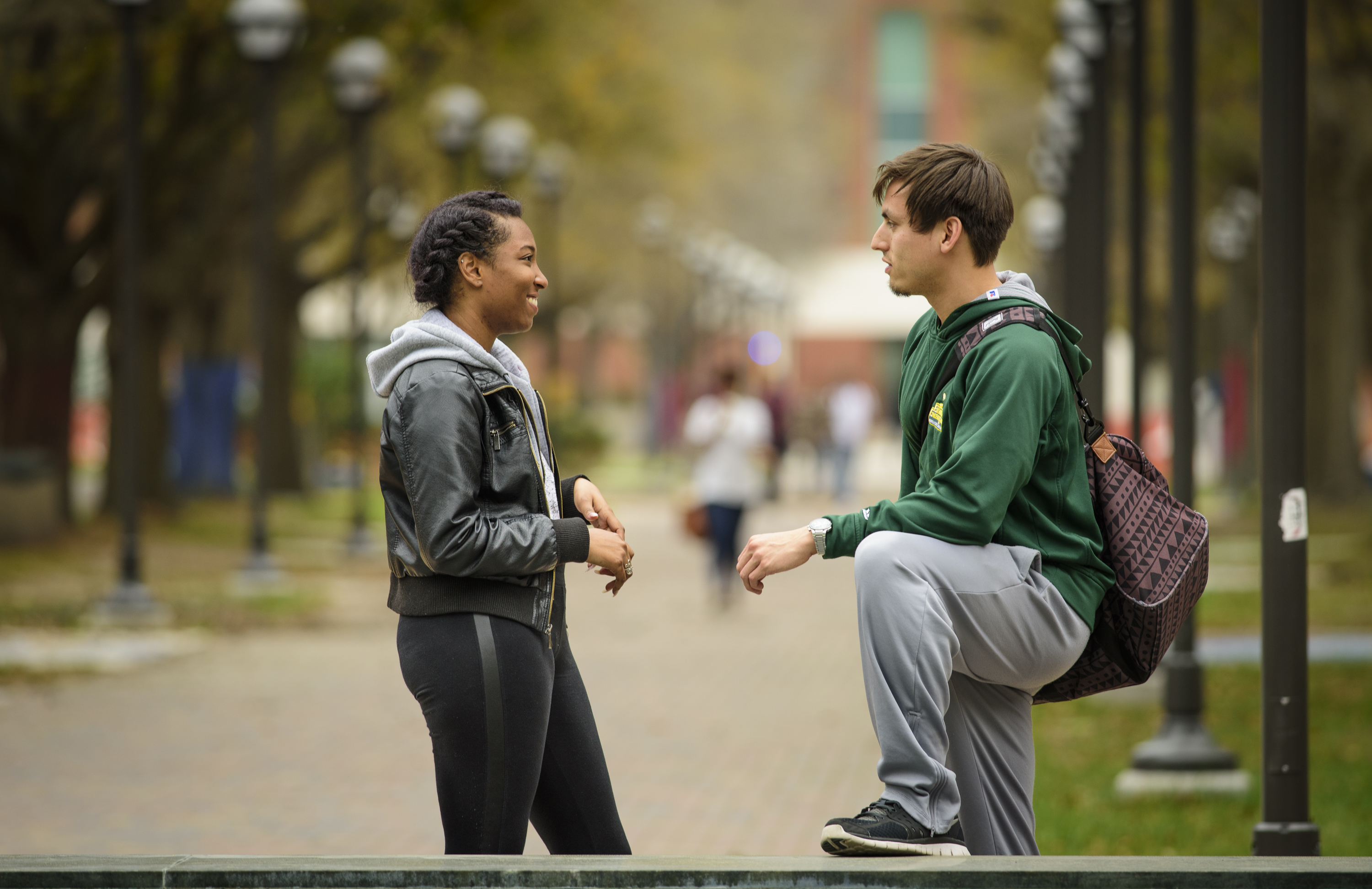 Picture of two students talking by a bench
